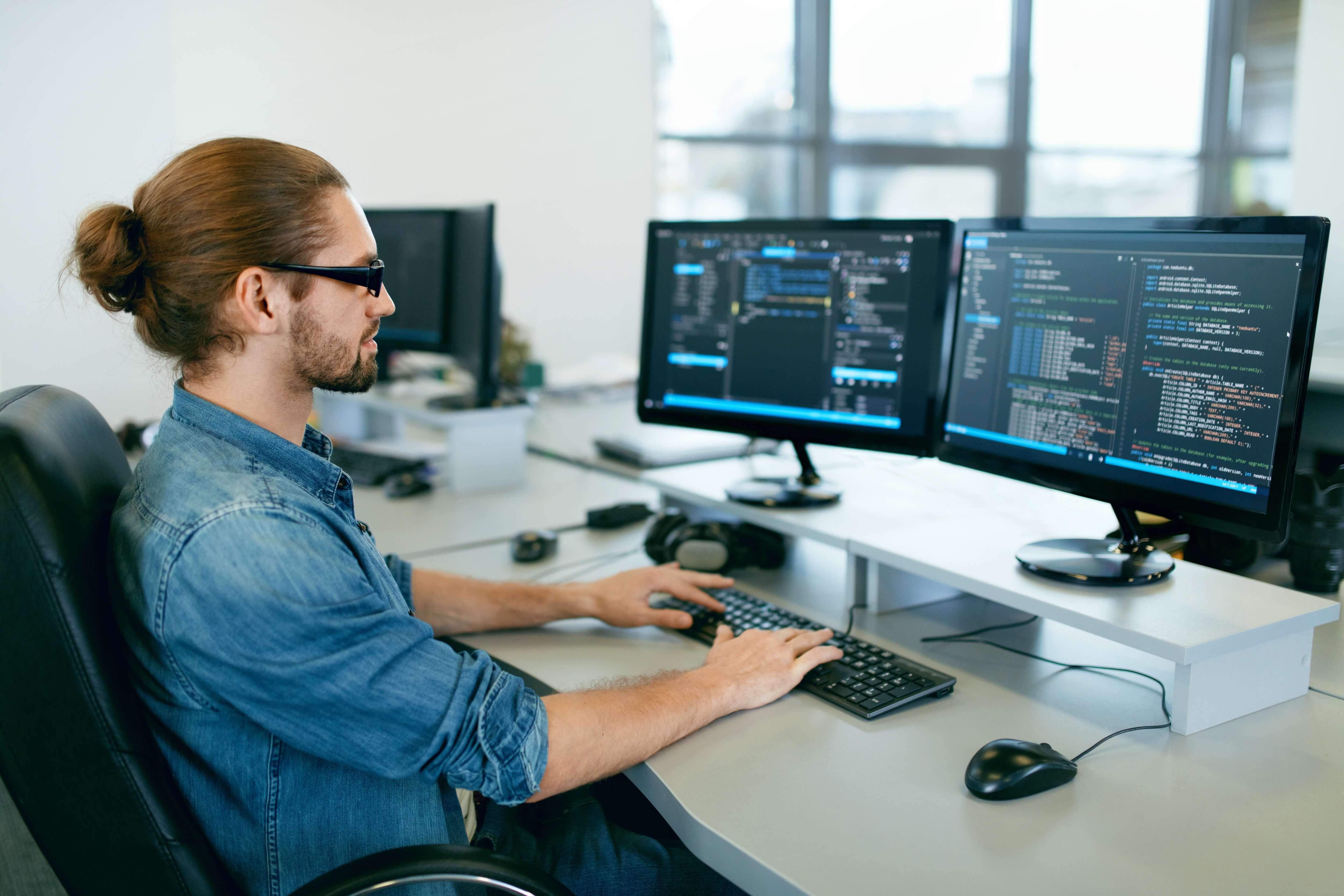 Man sitting at a desk programming software